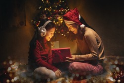 Asian mother and daughter open Christmas Lighting Present Gift Box front of Xmas Tree. Happy asia Mother with kid girl in Magic Night. Family merry christmas and newyear holiday concept.