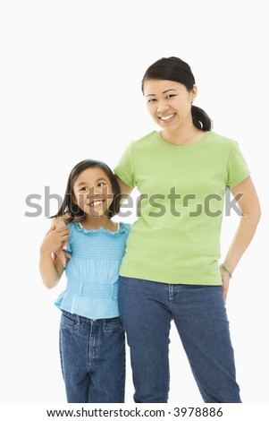 Asian mother and daughter standing with arms around each other.