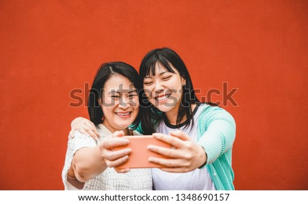 Asian mother and daughter taking selfie with smartphone for story app - Happy family people having fun with technology trends - Love, parenthood lifestyle, tech and tender moments concept #1348690157