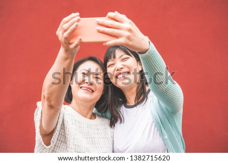 Asian mother and daughter taking selfie with smartphone for story app - Happy family people having fun with technology trends - Love, motherhood lifestyle, tech and tender moments concept #1382715620