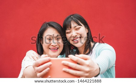 Asian mother and daughter taking selfie with smartphone for story app - Happy family people having fun with technology trends - Love, motherhood lifestyle, tech and tender moments concept #1464221888