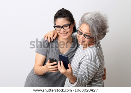 Asian mother and daugther in the white background. #1068020429