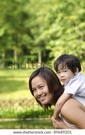 Asian mother and son having fun in park - stock photo