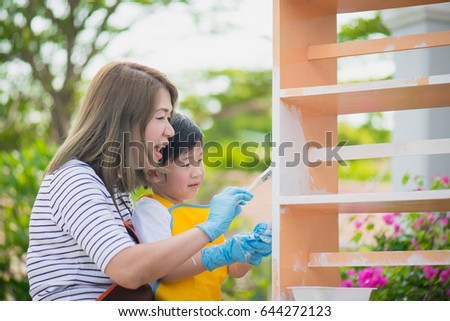 Asian mother and son painting wooden shelf together #644272123