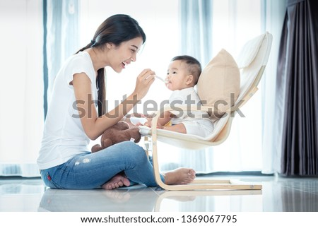 Asian mother feeding to her baby in leving room