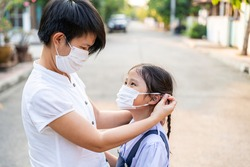 Asian mother help her daughter wearing medical mask for protection covid 19 or corona virus outbreak situation. Covid 19, Corona, Virus outbreak, healthcare and medical, pm 2.5 or Asian family concept