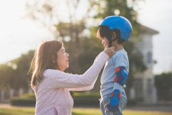 Asian mother helping her son wears blue helmet on enjoying time together in the park