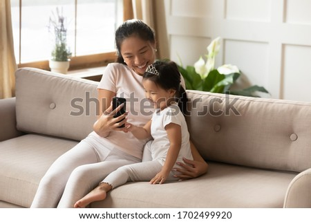 Asian mother hold smart phone showing to little daughter entertainment application having fun at home. Family using new cool educational app for kids. Concept of children development, parental control
