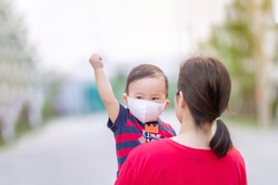 Asian mother holding her baby walking with wearing a dust mask protect for PM2.5 and as protection new virus COVID-19, Cute baby raised hand up with fist.
