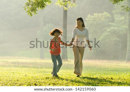 Asian mother holding her daughter's hand walking in the park #142159060