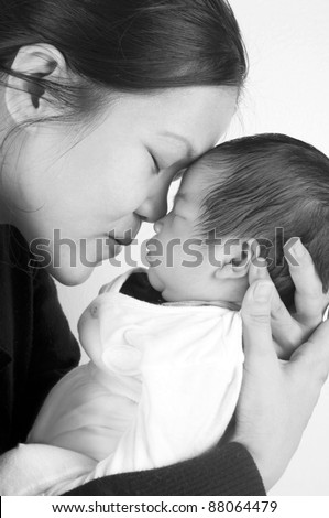 Asian mother holding her new born baby in sepia tone