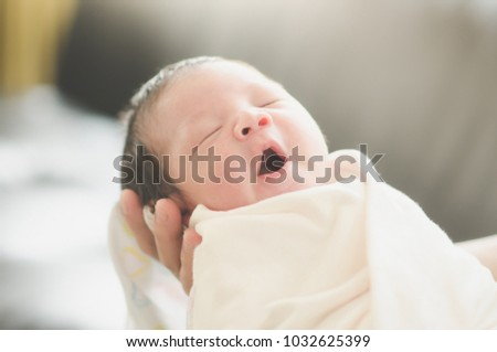 Asian mother is holding her sleeping newborn baby