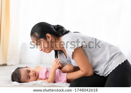 Asian mother is wiping the body of his little baby boy to reduce the body temperature from the fever, concept of home remedies for child illness by parent in family life, motherhood and love of mom. Stockfoto ©