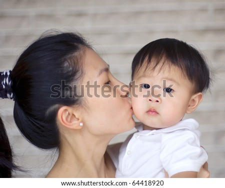 asian mother kissing her baby boy