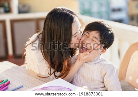 Asian mother kissing his little son outdoor on patio - Mother and child love