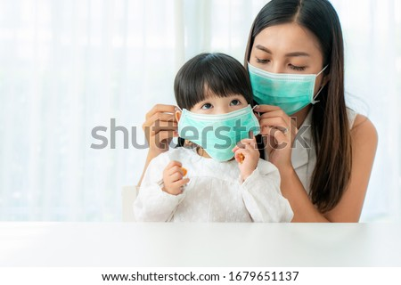 Asian mother wearing wearing to her daughter healthy face mask sitting in living room at home to prevent PM2.5 dust, smog, air pollution and COVID-19. Healthcare concept.