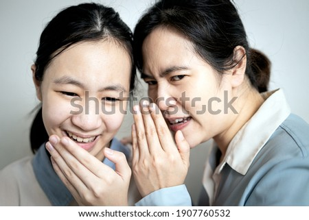Asian mother whispering gossiping in her daughter ear,adult woman look at other with disdain,aversion,telling a secret to slandering others to teen girl,facial expression of disapproval or irritation Photo stock ©