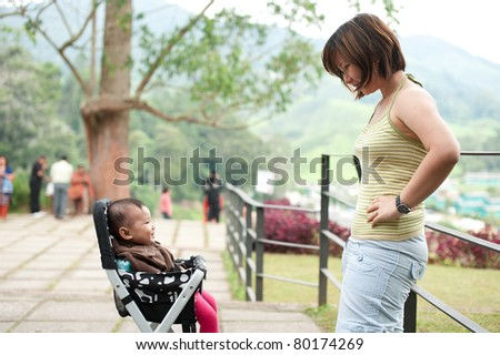 Asian mother with her 7 month old baby girl - stock photo
