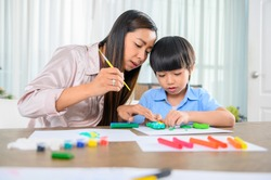 Asian mother work home together with son. Mom and kid play dough. Child creating plasticine clay model. Woman lifestyle and family togetherness activity.