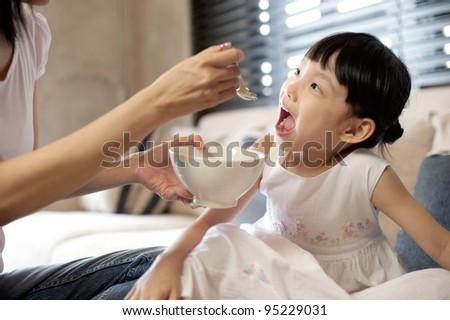 Asian Mum Feeding Child