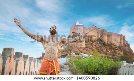 Asian muscled fit male model posing in pride outdoor showing his abdominal muscles with mehrangarh fort of jodhpur in background - Image