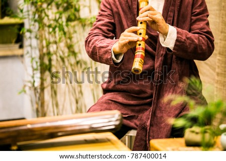 Asian musician in red clothes playing the Japanese flute #787400014