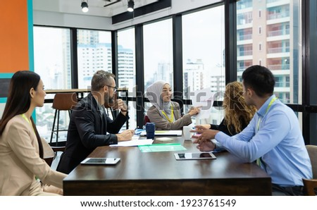 Asian Muslim business woman in hijab headscarf sitting on wheelchair presenting of her work to corporate colleagues in meeting in the modern office. diverse corporate colleagues and multicultural Stock fotó ©