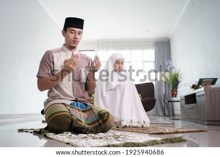 asian muslim husband and wife praying jamaah together at home