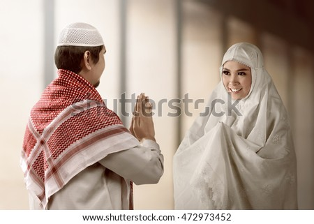 Asian muslim man and woman greet each other with muslim tradition asian muslim man and woman greet each other with muslim tradition with mosque background m4hsunfo