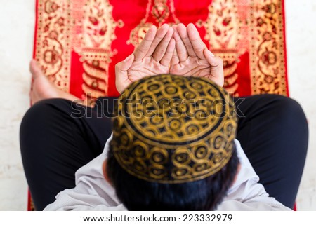 Asian Muslim man praying on carpet wearing traditional dress