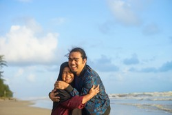 Asian Muslim mother and son hugging with love at the beach/ Muslim mother and son/ Malaysian/ Indonesian mother and son