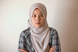 Asian muslim woman wearing hijab looking at camera with neutral expression, diverse people portrait concept