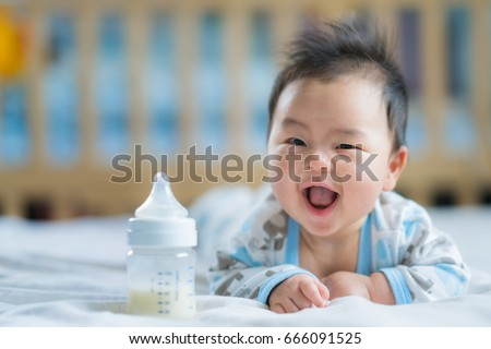 Asian Newborn baby smile with milk power bottle, baby, boy, mom, mother concept