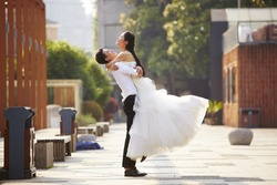 asian newly wed bride and groom celebrating marriage and hugging outside a building.