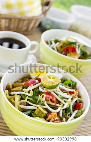 Asian noodles on bamboo mat with focus pointed in front of dish and shallow DOF - stock photo