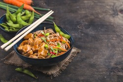 Asian noodles with chicken, vegetables in bowl, rustic wooden background. Space for text. Soba noodles, teriyaki chicken, edamame, chopsticks. Closeup. Asian style dinner. Chinese/Japanese noodles