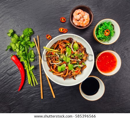 Asian noodles with spicy soy sauce and chicken pieces, top view, served on black stone. #585396566