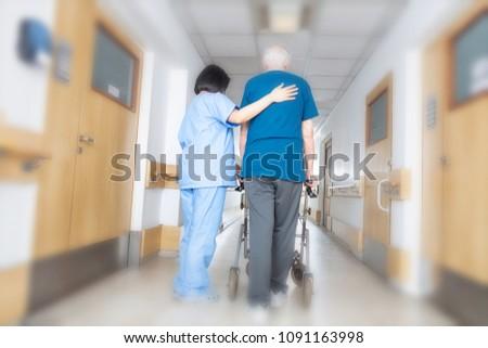 Asian nurse helping elder man walking in rehab facility.