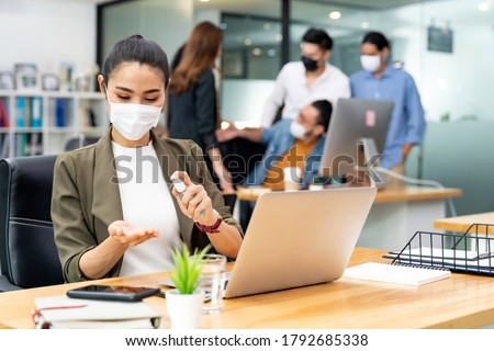 Asian office employee businesswoman wear protective face mask use alcohol spray hand sanitiser for hygiene in new normal office with social distance practice prevent coronavirus COVID-19 spreading.