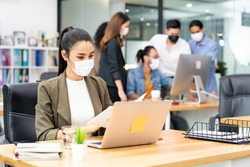Asian office employee businesswoman wear protective face mask work in new normal office with interracial business team in background as social distance practice prevent coronavirus COVID-19 spreading.
