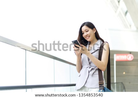 Asian office girl playing mobile phone standing on elevator in shopping mall. She is smiling and enjoy using the smartphone in her lifestyle. Technology and lifestyle concept.