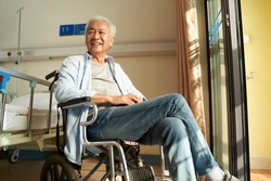 asian old man sitting in wheel chair in nursing home or hospital ward looking happy and content