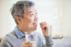 asian old man take medicine  at home