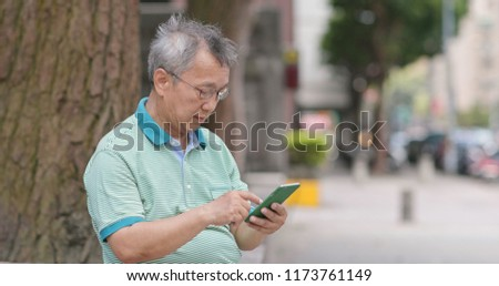 Asian old man use of mobile phone at outdoor