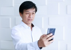 Asian old middle aged confident handsome black hair male businessman wears white long sleeve shirt has farsightedness optical problem when try to read short message from small smartphone screen.