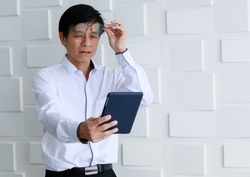 Asian old middle aged handsome stress black hair male businessman wears white long sleeve shirt has presbyopia farsightedness optical problem when hold eyeglasses try to read sms from tablet screen.