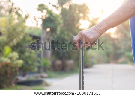 Asian old woman standing with his hands on a walking stick,Hand of old woman holding a staff cane #1030171513