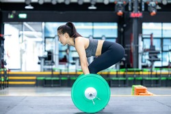 Asian oman weightlifter preparing for training, Asian woman workout weightlifting in weight training fitness gym, sport exercise and muscular build, healthy lifestyle