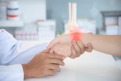 Asian orthopaedic doctor doing physical examination in the patient with wrist pain at the clinic. Pain from tendinitis and sport injury. Selective focus at wrist with red hi light. Medical concept