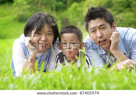Asian outdoor family lying on green field